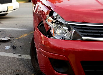 Closeup of a red car with a smashed headlight from a collision with another car